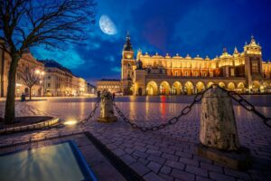 Krakow Main Market Place After Dark with Moon on the Sky. Cracow, Lesser Poland, Europe.